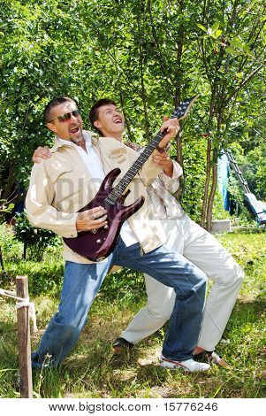 The Man And The Guy On The Nature In The Summer With An Electroguitar