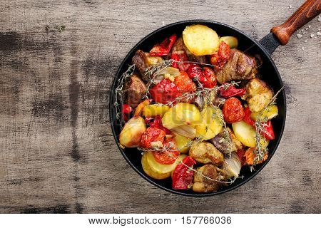 Fried meat with vegetables in a cast iron pan on a wooden table top view with copy space