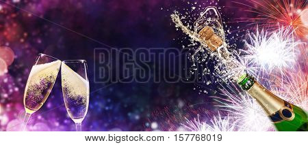Splashing bottle of champagne with glasses over fireworks background. Celebration concept, free space for text