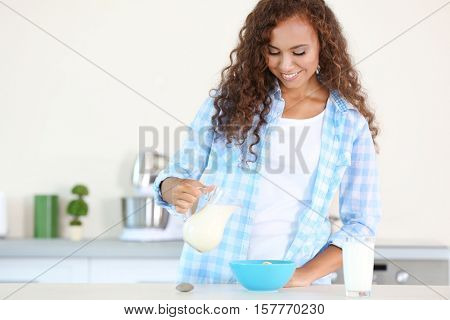 Beautiful young African-American woman pouring milk in the kitchen
