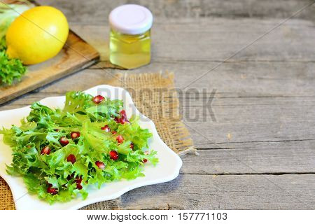 Frisee lettuce leaves with pomegranate seeds dressed with lemon juice and olive oil. Easy salad recipe. Diet vegan salad on a plate, ingredients for salad on wooden background with copy place for text