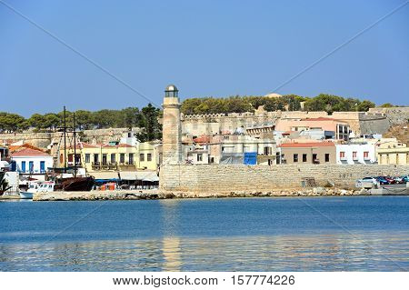 RETHYMNO, CRETE - SEPTEMBER 15, 2016 - View of the harbour and lighthouse with the castle to the rear Rethymno Crete Greece Europe, September 15, 2016.