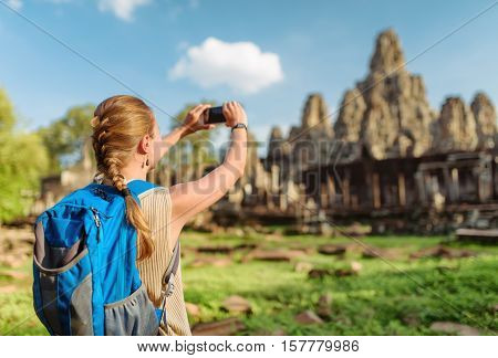 Female Tourist Taking Picture Of Bayon Temple. Angkor, Cambodia