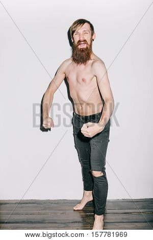 Portrait of a skinny man on a white background flexing for camera
