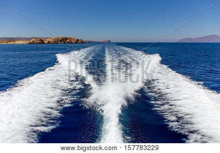 Fast moving boat wake in mediterranean sea and island on background