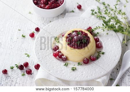 Cheesecake, cottage cheese pudding with cranberry jam, fresh cranberries and thyme on a white plate on a old white background, selective focus