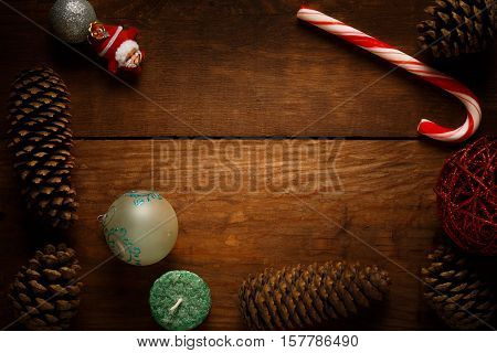 Beautiful christmas frame decoration from peppermint candy cane stick christmas balls candle santa claus decor fir cones and pinecones at brown wooden background.