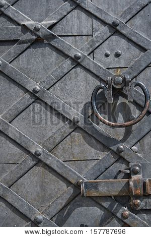 A fragment of an old wooden door with metal handle and bolt. Door strengthening iron strips. Texture background