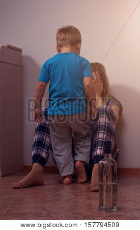 Little boy standing next to his drunk mother. Alcoholic addiction child abuse. Bottle and glass shallow depth of field.
