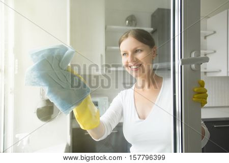 Beautiful smiling young housewife doing house chores, washing the windows, wearing rubber protective yellow gloves, with rag and spray bottle detergent. Home, housekeeping concept