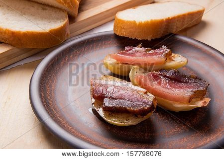 Close Up View Of Baked Potatoes With Slices Of Bacon On Wooden Background.