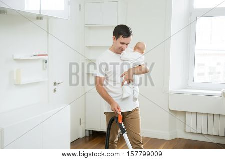 Smiling stay-at- home dad spending time together with his little child, doing vacuum cleaning carpet in living room, holding a baby in one hand and vacuum cleaner in another. Home, housekeeping concept.