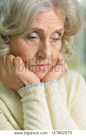 Portrait of bored senior woman with hands under her chin