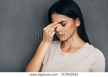 Feeling tired and stressed. Frustrated young woman massaging her nose and keeping eyes closed while standing against grey background