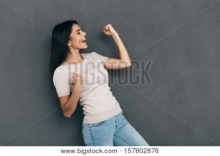 Used to success. Happy young woman in casual wear gesturing and keeping eyes closed while standing against grey background