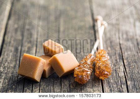 Brown sugar crystals on stick and caramel candies on old wooden table.