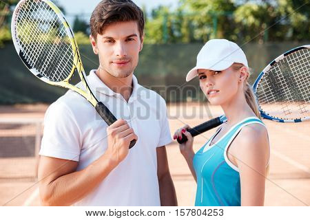 Close up tennis couple on court. with rackets. looking at camera