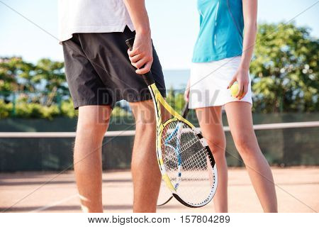 Legs of tennis couple on court. cropped image