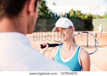Young tennis couple. image from behind of man. man is blur