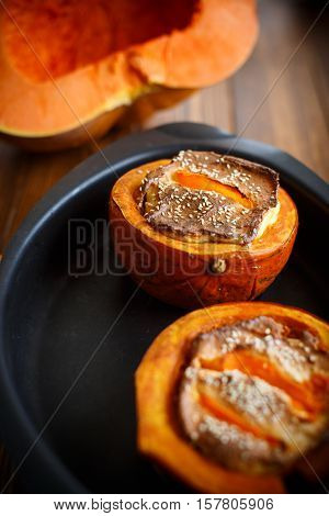 Pumpkin baked with cheese and sesame seeds on a baking sheet