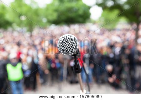 Protest. Microphone in focus against blurred crowd. Public demonstration.