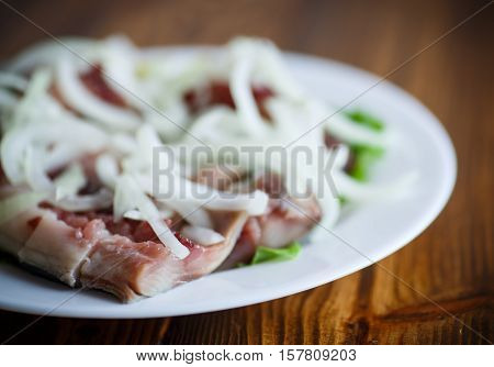 salted herring with onions on the table