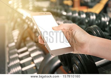 Female hand with smartphone against blurred gym equipment background
