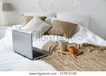 technology, holidays, christmas and winter concept - cozy bedroom with laptop computer, coffee cup and croissant on bed at cozy home