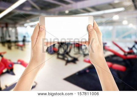 Female hands with smartphone against blurred gym interior background