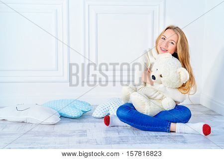 Happy girl teenager sitting in a cozy room with her lovely teddy bear and beautifully smiles. Healthy beautiful straight teeth, the correction of bite. Orthodontic treatment. Dental care.