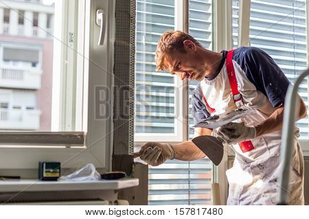 Construction worker wearing worker overall with wall plastering tools renovating apartment house. Plasterer renovating indoor walls and ceilings with float and plaster. Construction finishing works.
