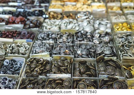 Vintage clothes buttons in silver and gold colouring for sale in the most famous flea market in Chinatown district Bangkok Thailand