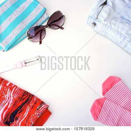 Jeans, t-shirt, striped socks, sandals, and sunglasses and belt on a light background. Flat lay, top view