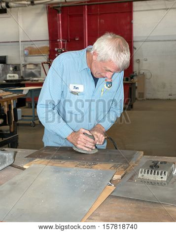 DAYTON, OHIO, USA - NOVEMBER 18, 2016: Restoration worker at the National Museum USAF is shown here buffing a piece of aluminum to be used in restoring the Memphis Belle B-17F bomber.
