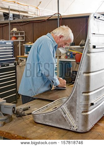 DAYTON, OHIO, USA-NOVEMBER 18, 2016:Restoration worker at National Museum USAF is shown here buffing piece of aluminum to be used in restoring the Memphis Belle's co-pilot seat, shown in foreground.