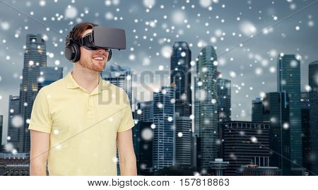 technology, augmented reality, winter, christmas and people concept - happy young man with virtual headset or 3d glasses over singapore city skyscrapers background and snow