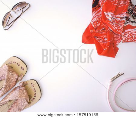 Sunglasses, sandals, pareos and strap on a light background. Flat lay, top view