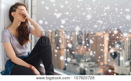 people, emotion, winter, christmas and teens concept - sad unhappy pretty teenage girl sitting at window over city background and snow