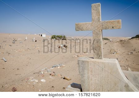 Abandoned graveyard with crumbling stones and crosses in Namib Desert of Angola. The sand is slowly claiming the site back and it seems forgotten and abandoned.