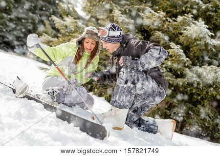 Young man snowboarder helps a beautiful young female skier who fell down on mountain slope.