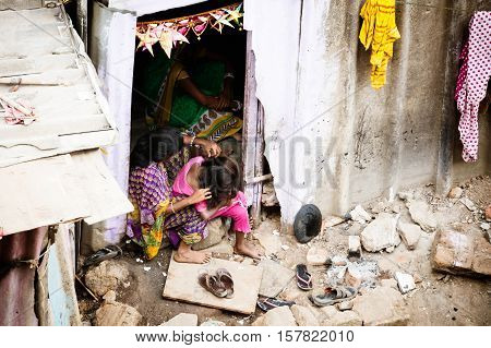 A woman checks the hair of a child in a slum in the district of Airoli in Mumbai, India