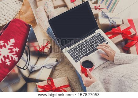 Christmas online shopping top view. Female buyer with laptop, copy space on screen. Woman has coffee, buys presents, prepare to xmas eve, sitting among gifts boxes and packages. Winter holidays sales