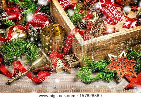 Christmas decorations box with stars toys and ornaments. Festive composition vintage toned falling snow effect