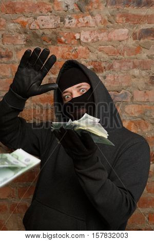Robber in mask throws banknotes