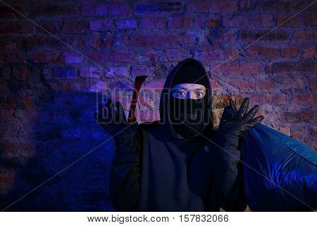 Astonished bandit near brick wall