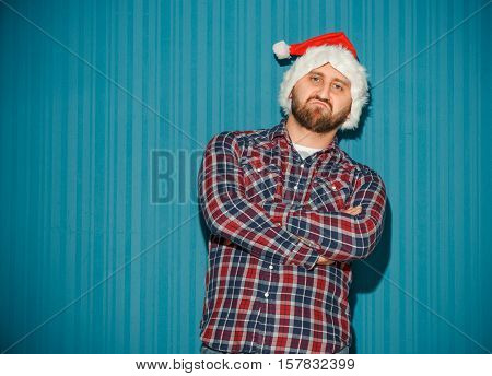 The opinionated christmas man wearing a santa hat on the blue studio background