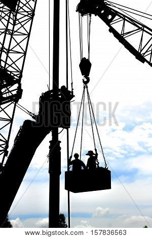 construction worker with use crane hook carry workers to work at site construction
