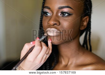 beautiful african model preparing to shooting. Make up artist doing make up using profesional makeup brush. Black woman with white lips