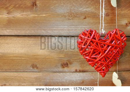 Braided red dangling heart on wooden background