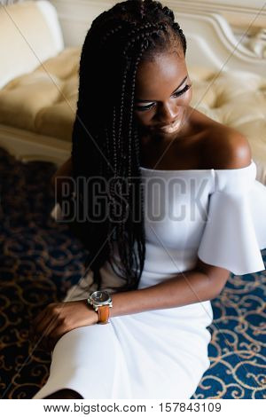 incredible african woman sitting on the floor in vip europian hotel. Hotel room with classic interior